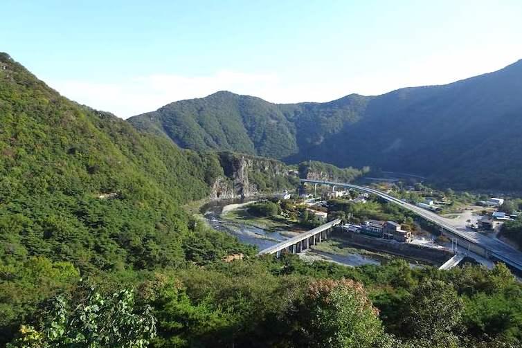 姑母山城の頂上からの眺め。道路や川が谷間を走る交通の要衝